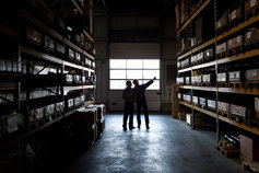 Two workers in a metal parts warehouse