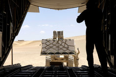 A forklift loading cargo onto military plane