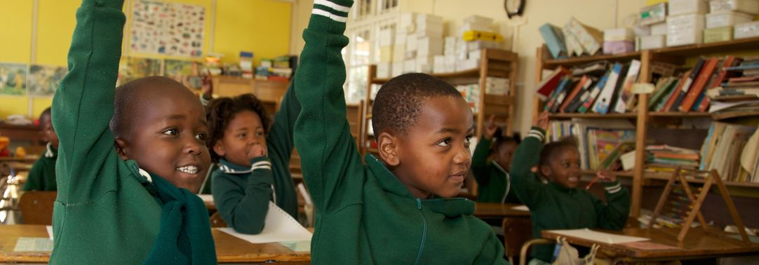 School children raising their hands