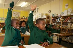 Young schoolchildren raise their hands in air