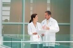 doctors-talking-together-near-hospital-railing