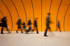 Group of people walking through a modern orange subway