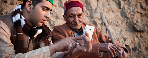 young man showing phone to grandfather