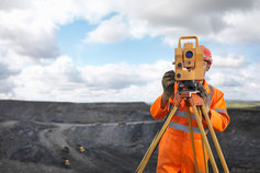 Surveyer with open cut mine in the background