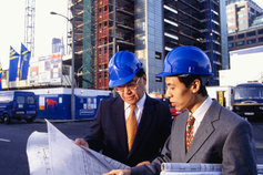 architects discussing blueprint on construction site