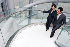 Two business people climbing stairs