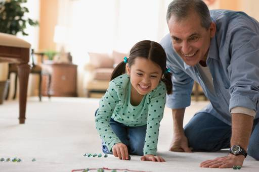Grandfather and granddaughter playing marbles on