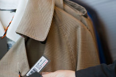 Hand looking at a price tag on a coat