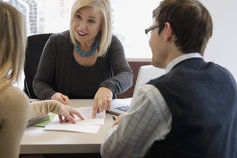 KPMG Accounting Advisory Services image: Three people discussing a document.