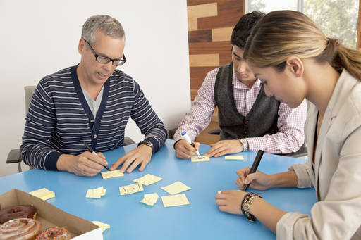 Business people writing on post its
