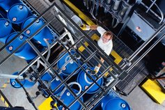 Worker in chemical plant filling blue drums