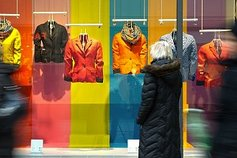 People walking past colourful clothing shop window