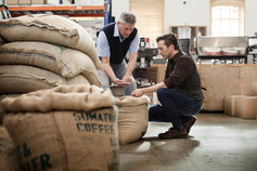two men inspecting coffee beans