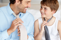 Father showing son to knot a tie