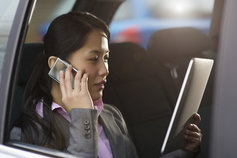 Businesswoman using phone and tablet in car