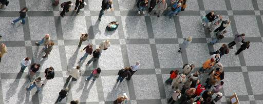 People standing on a footpath patterned with grey squares