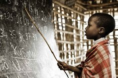A boy solving a problem on a chalkboard
