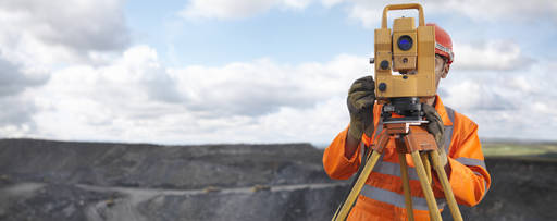 Man looking through surveying equipment at a quarry