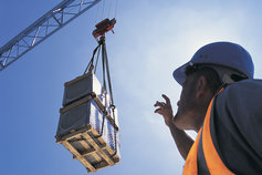 KPMG IFRS Newsletter: The Balancing Items publication cover image: a construction worker looks up at a crane moving a heavy load.