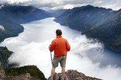 KPMG IFRS Business Combinations topic image: hiker looking down at clouds over a lake.