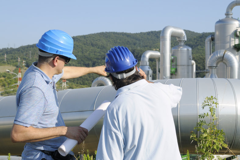 Hard-hatted energy workers discussing environmental due diligence