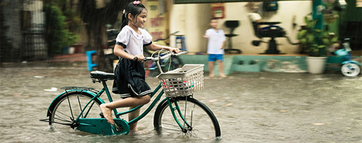 Girl on bicycle stuck in water