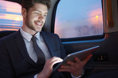 man working on ipad while sitting in car