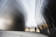 Man walking down a silver walled alley