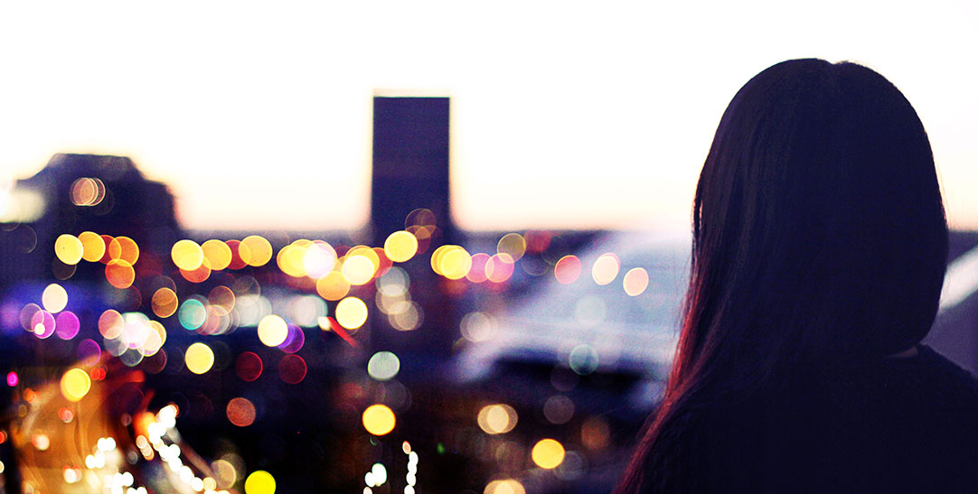 Woman looking at the city from the balcony