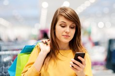 KPMG 'New revenue standard: A clearer view of IFRS 15' publication image: Woman looking at a smartphone while carrying shopping bags.