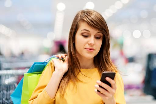 Woman with shopping bags looking at mobile