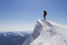 KPMG 'The future of IFRS' topic image: Climber on summit of snow capped mountain.