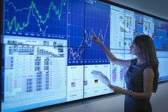 Business woman pointing at graph on digital screen