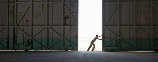 Worker opening large warehouse door