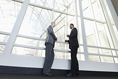 Two men standing in front of glass building