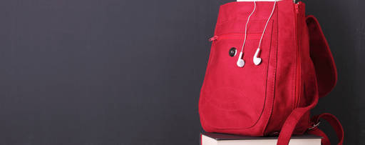 Digital tablet in a red backpack in front of blackboard