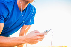 Caucasian runner resting and listening to mp3 player