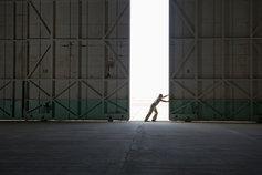 Caucasian worker opening large warehouse doors