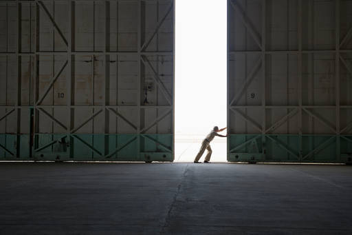 Worker opening warehouse doors