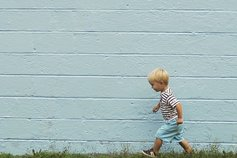 Little boy walking on grass in front of blue wall