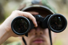 Close-up of young soldier with binoculars