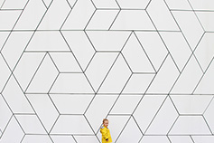 Girl (2-3) in yellow raincoat against white wall