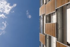 looking-up-at-an-apartment-building-exterior-with-wood-and-steel-shutters