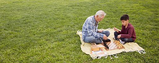 An older man and child playing chess on a picnic blanket in a park