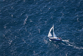 Sailboat sailing on dark blue sea