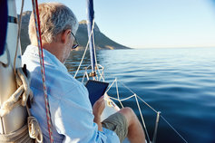 Sailing man on yacht reading tablet