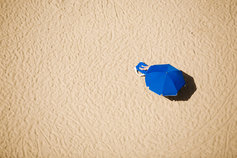 Blue umbrella on sandy beach