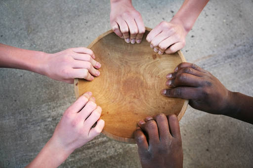 empty wooden bowl multi cultural hands