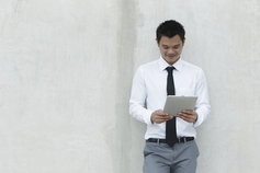 man standing on a wall holding tablet