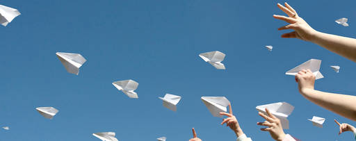 Children throwing paper planes in the air